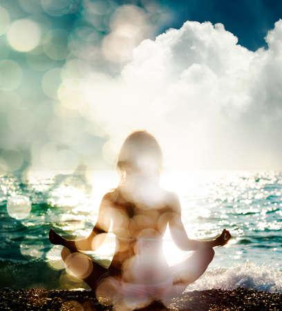 女性は、自然の背景にヨガの練習します。後姿。精神的、魂のコンセプトです。健康的なライフ スタイル。二重露光は、ボケ味を持つ写真をフィルタ リング。 写真素材