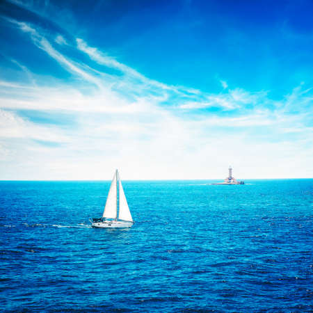 bakground: Beautiful Seascape with White Yacht Sailing in Calm Blue Sea. Clouds and Lighthouse on the Bakground. Toned and Filtered Photo with Copy Space. Stock Photo