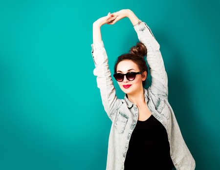 Happy Hipster Girl in Sunglasses and Jeans Shirt Posing at Turquoise Background. Street Style Fashion Outfit. Toned Photo with Copy Space.