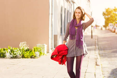 fashionable woman: Beautiful Smiling Girl Walking in the Street of European City. Trendy Urban Fashion Style in Spring or Autumn. Toned Photo with Copy Space. Stock Photo