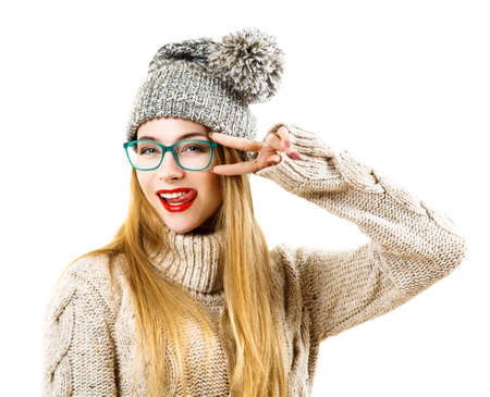 Funny Hipster Girl in Knitted Sweater and Beanie Hat Going Crazy. Isolated on White. Trendy Casual Fashion Outfit in Winter. Standard-Bild