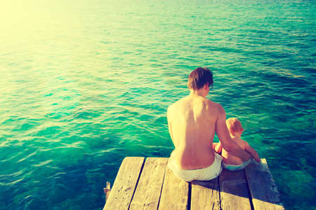 water ripple: Young Father with His Little Baby Sitting on the Pier and Relaxing by the Sea. Rear View. Ripple Water Background. Dad and Son Concept. Warm Toned and Filtered Photo. Stock Photo