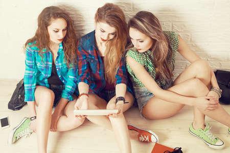 pantalones cortos: Tres muchachas de los estudiantes sienta en el suelo y Lokking en la tableta. Adolescentes de moda estilo de la calle. La manera del equipo casual. Amistad concepto de juventud y estilo de vida. Vista superior. Foto tonos.