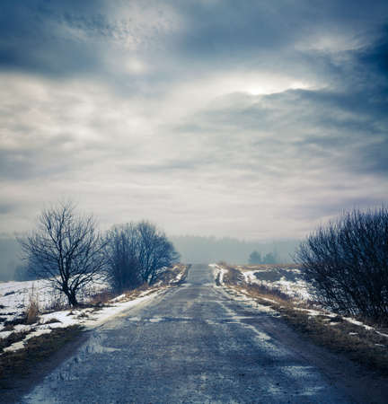 Winter Landscape. Dirty Road, Fog and Moody Sky. HDR Styled Clouds. Toned Photo with Copy Space. Stock Photo