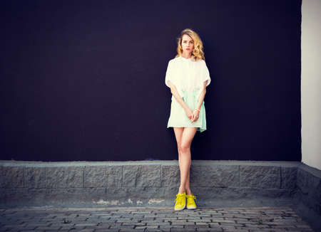 Full Length Portrait of Trendy Hipster Girl Standing at the Dark Textured Wall Background. Urban Fashion Woman Concept in Summer. Street Style. Toned Photo with Copy Space.
