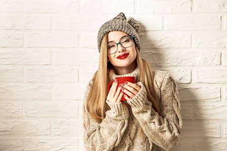 Romantico inverno Hipster Girl in maglione lavorato a maglia e cappello Beanie gustare una tazza di tè caldo in mano. Bella donna sognare. Sfondo bianco muro di mattoni. Riscaldamento Concept. Tonica foto con spazio di copia. Archivio Fotografico - 65115696