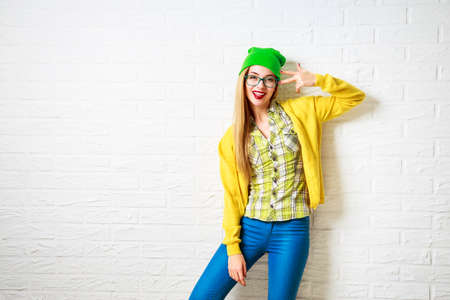 Funny Hipster Girl at White Brick Wall Background. Banco de Imagens