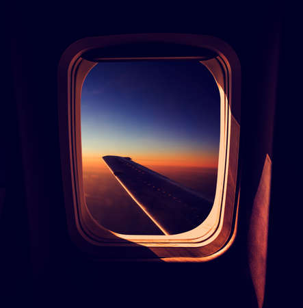 View from Airplane Window at Sunset. Calm and Sleepy Mood in Air Travel Concept. Dark Atmospheric Toned Photo.