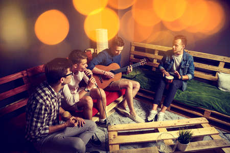 Group of Four Friends Hanging Out in Studio. Guys Singing and Playing Music in Urban Apartment. Toned Photo with Bokeh.
