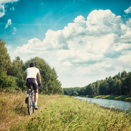 Rear View of a Cyclist Riding a Bike on River Bank. Healthy Lifestyle and Leisure Activity Concept. Toned and Filtered Instagram Styled Photo with Copy Space. Stock Photo