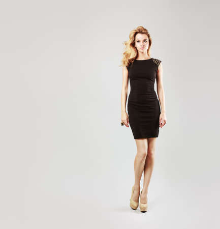 Full Length Portrait of a Beautiful Blonde Woman in Little Black Fashion Dress. Gray Background. Toned Photo with Copy Space. photo