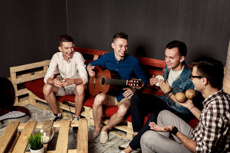 grupo de hombres: Grupo de cuatro amigos sonrientes felices colgando hacia fuera en estudio. Chicos cantando y tocando música en apartamento urbano. Foto entonada con Bokeh. Foto de archivo