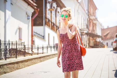 유럽 도시에서 행복 웃는 패션 여자. 트렌디 한 Hipster 소녀 선글라스와 여름 복장에 써니 스트리트에 산책. 복사 공간 톤된 사진입니다.