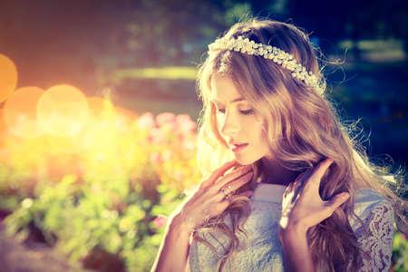 Novia romántica con la tiara de boda en el fondo la naturaleza caliente. Estilo nupcial moderna. Foto natural. La foto en tonos de bokeh y Espacio.