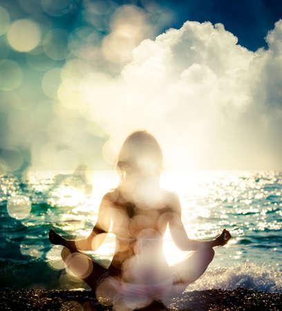 Yoga practicante de la mujer por el mar. Silueta de una chica delgada. La naturaleza de fondo con el bokeh de la luz del sol. Meditación, espiritual y concepto del alma. Estilo de vida saludable. Exposición de fotos doblemente filtrado.