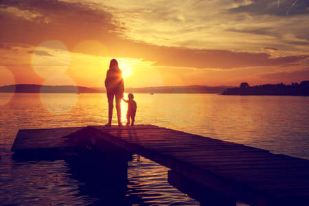mom son: Silhouettes of Young Mother and Her Little Baby Standing on the Pier and Watching Sunset by the Lake. Happy Family Lifestyle. Motherhood and Childhood. Mom and Son. Toned Photo with Bokeh. Copy Space.