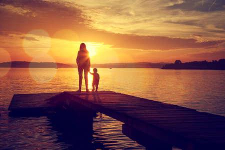 mama e hijo: Siluetas de la madre joven y su pequeño bebé que se colocan en el muelle y viendo la puesta del sol por el lago. Feliz estilo de vida familiar. La maternidad y la infancia. Mamá e hijo. Foto entonada con el bokeh. Espacio en blanco.
