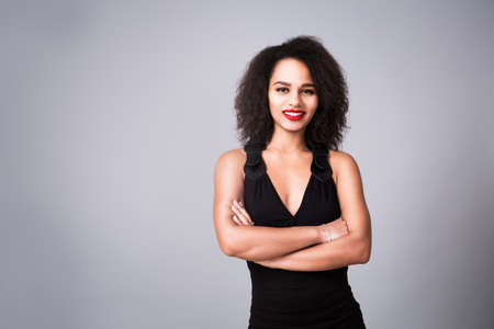 Portrait of Happy Fashion Woman in Black Dress on Gray Background. Beautiful Mixed Race Girl Smiling. Female with Curly Hair and Red Lipstick. Toned Photo with Copy Space.