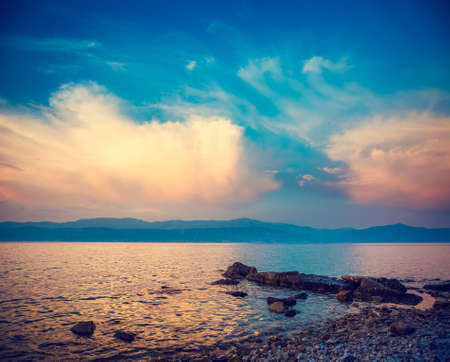 Beautiful Sea with Blue Sky and White Clouds at Sunset. Pebble Beach in Croatia, Europe. Evening Seascape in Dalmatia, Adriatic Sea. Coastline and Mountains on the Horizon. Toned and Filtered Photo.