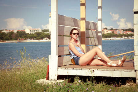 descansando: Young Girl Relaxing by the Sea. Beautiful Slim Woman in Sunglasses Resting Outdoors. Summer Vacation. Retro Toned Photo.