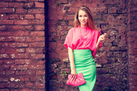 Happy Fashion Woman Standing at the Old Red Brick Wall Background. Glamour Girl Outdoors. Beautiful Female in Pink Blouse and Green Skirt. Toned Photo with Copy Space.