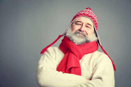 man with beard: Portrait of Serious Old Man with Beard in Funny Red and White Winter Clothes on Gray Background. Modern Mature Man Concept. Toned Photo with Copy Space. Stock Photo