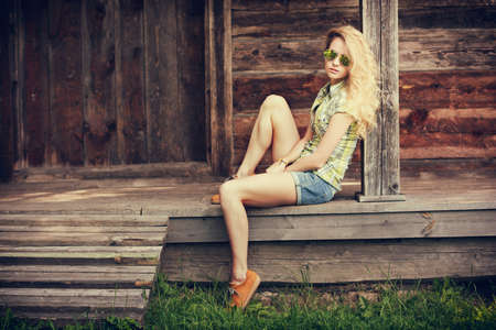 Trendy Hipster Girl Sitting on the Wooden Porch and Looking at Camera. Beautiful Street Style Fashion Woman in Sunglasses Outdoors. Toned and Filtered Photo with Copyspace. Wooden Background.