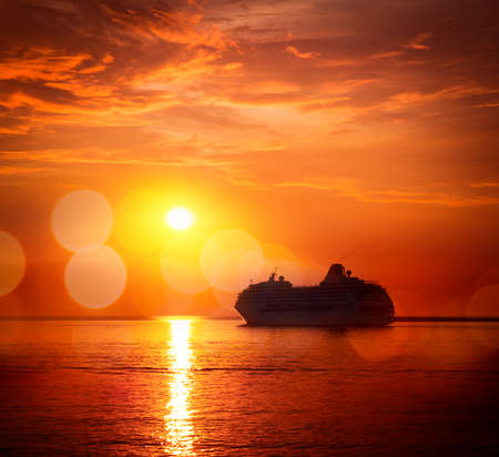 Silhouette of Cruise Ship at Sea. Beautiful Seascape Sunset Background. Romantic and Luxury Travel Concept. Toned and Filtered Photo with Bokeh. Copyspace.