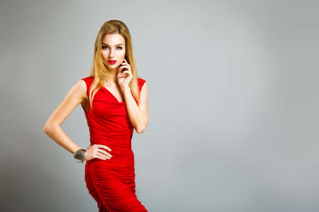 Beauty Portrait of Sexy Blonde Woman in Red Dress on Gray Background. Long Hair. Holiday Fashion Female Makeup. Smoky Eyes and Red Lipstick. Glamour Girl. Toned Photo with Copy Space. Banco de Imagens
