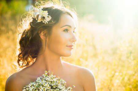 iluminado a contraluz: La muchacha inocente joven al aire libre en el fondo de la naturaleza. Manera de la boda peinado y accesorios. Hermoso retrato de mujer. Cándida novia de fotos. La puesta del sol puesto a contraluz encienden. La foto en tonos Espacio en blanco.
