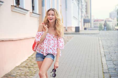 Laughing Fashion Woman na ulicy miasta w Europie. Uśmiechnięta Modne Dziewczyna w Letnich Europejskich Town. Szczęśliwy Portret żeński. Skopiuj miejsce.