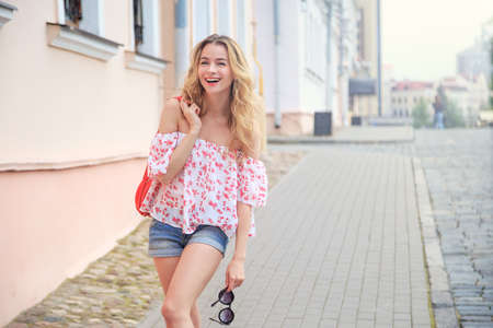 Laughing Fashion Woman in the City Street in Europe. Smiling Trendy Girl in Summer European Town. Happy Female Portrait. Copy Space.