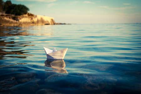 紙の船が海に浮かぶ。折り紙紙のボート セーリング。美しい波リップル背景。異常な旅行の概念。コピー スペースとトーンとフィルター処理された