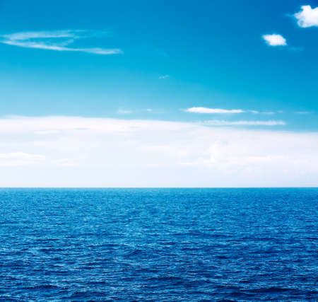 Beautiful Blue Sea and White Clouds in the Sky. Summer Seascape with Clear Water. Ocean View. Copy Space Background. Toned Photo.