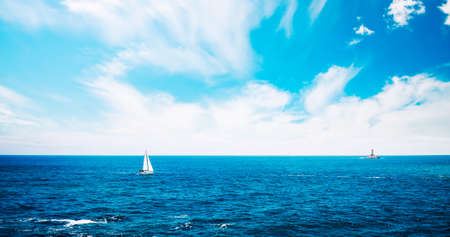 Summer Seascape with Clear Blue Water. Sailing Yacht and Lighthouse Porer on Horizont. Croatia, Europe, Adriatic Sea. Mediterranean Sea Vacation. Copyspace Background. Toned and Filtered Photo.
