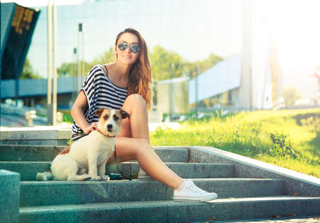 Happy Hipster Girl with her Dog in the City Park. Smiling Woman with Pet Outdoors at Sunset. Trendy Fashion Female. Toned and Filtered Photo. Modern Youth Lifestyle Concept.