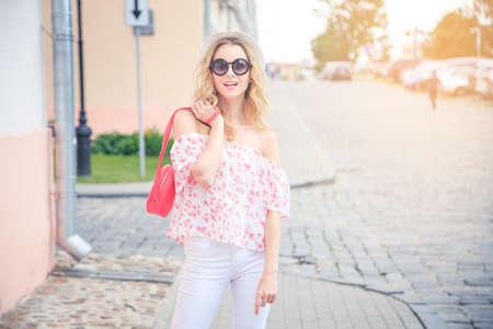 Leende modekvinna i Gamla stan i Europa. Glad trendig tjej i runda solglasögon på sommaren. Tonat foto med kopieringsutrymme och vackert solljus.