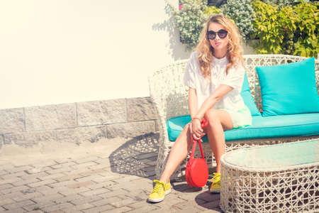 Young Fashion Woman Outdoors. Trendy Street Style Girl in Summer Clothing and Sunglasses Sitting. Toned Photo with Copy Space.