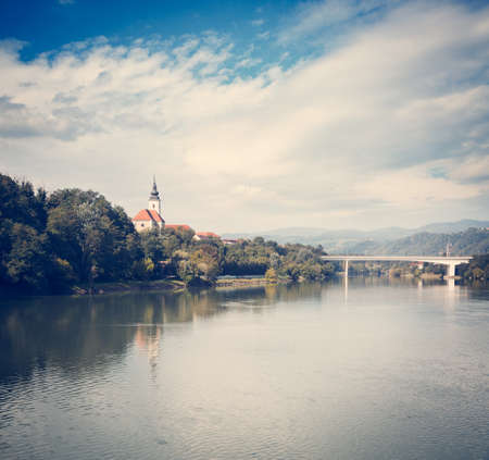 Old Church on River Bank on Mountains Background. Typical Landscape in Slovenia. St. Joseph Church in Maribor on Drava River. Popular Touristic Destination in Slovenia, Europe. Toned Photo. Stock Photo