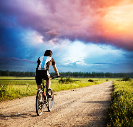 Man Riding a Bike on Country Road at Stormy Sunset. Cyclist Rear View. Dramatic Evening Clouds and Sky. Summer Nature Background. Healthy Lifestyle Concept. Toned and Filtered Photo and Copy Space. Banco de Imagens
