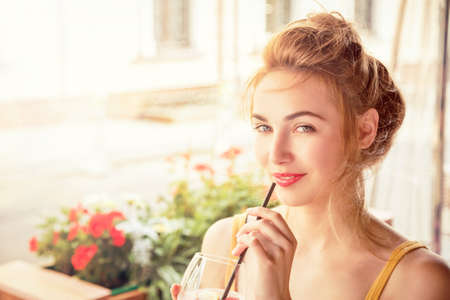 Fashion Girl Drinking Cocktail in a Cafe Terrace Outdoors. Smiling Trendy Woman in the City. Stylish Young Female. Toned Photo with Copy Space.