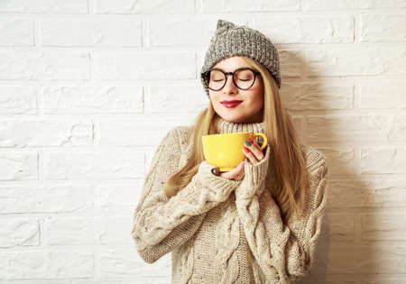 Romantic Winter Hipster Girl in Knitted Sweater and Beanie Hat Enjoying a Cup of Hot Tea or Coffee in Hands. Lovely Dreaming Woman. White Brick Wall Background. Toned Photo with Copy Space. photo