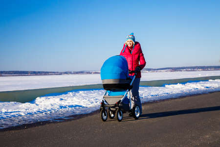 Happy Mother with Baby Stroller Walking in Winter Park and Enjoying Sunny Day. Snowy Background. Happy Parenting and Healthy Lifestyle Concept. Photo with Copy Space. Banco de Imagens