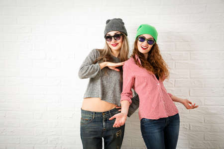 Two Happy Smiling Hipster Girls Posing at White Brick Wall Background. Trendy Casual Fashion Woman Outfit in Autumn or Spring. Teenage Female Friendship and Lifestyle. Toned Photo with Copy Space.