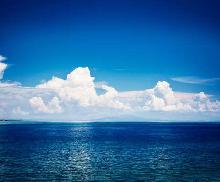 青い海と空と白い雲の反射。水平線上に島。透明な澄んだ青い水と夏の地中海海の風景。アドリア海の休暇の概念。空間の背景にコピーします。ト 写真素材