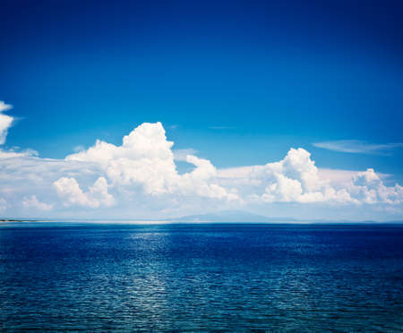 horizon reflection: Blue Sea with Sky and White Clouds Reflection. Islands on the Horizon. Summer Mediterranean Seascape with Transparent Clear Blue Water. Adriatic Vacation Concept. Copy Space Background. Toned Photo. Stock Photo