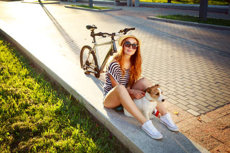 Smiling Hipster Girl with her Dog and Bike Relaxing in Park. Happy Woman Enjoying Summer Lifestyle with Pet. Candid Toned Photo with Copy Space. Banco de Imagens