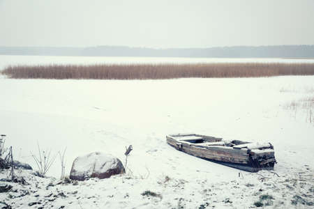 Winter Landscape. Abandoned Frozen Boat on a Lake Covered with Snow. Serenity and Tranquility Concept. Toned Photo with Copyspace. Banco de Imagens