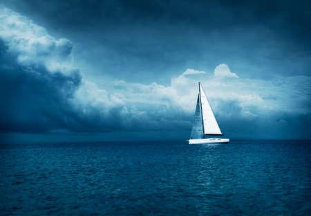 폭풍우 치는 바다에서 흰색 요트 항해입니다. 어두운 Thundery 밤 배경입니다. 극적인 폭풍우 Cloudscape입니다. 바다 개념에 위험입니다. 차가운 톤된 사진
