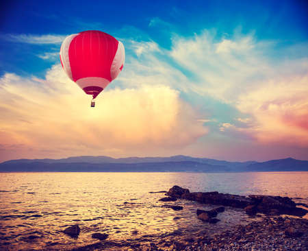 Hot Red Air Balloon Flying over Sea at Sunset. Blue Sky Background with Beautiful Clouds. Pebble Beach and Evening Seascape. Coastline and Mountains on the Horizon. Toned and Filtered Photo. Stock Photo